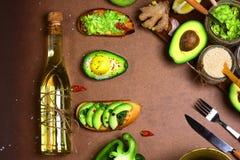 I panini, Bruschetta con l'avocado, verdure verdi pepano, limone, zenzero, aglio, olio, sale marino, insalata di rucola, olio d'o fotografia stock libera da diritti