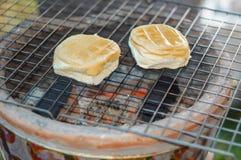 I panini con la crema dell'uovo hanno tostato sull'addetto alla brasatura del carbone Fotografie Stock