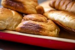I panini e le pasticcerie fragranti sono presentati in piatto di legno con la disposizione di cuoio immagini stock