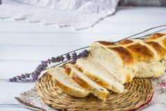 I panini trasversali caldi di Pasqua con lavanda fiorisce sul tovagliolo e sulla tavola bianca e viola di legno Immagine Stock