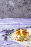 I panini trasversali caldi di Pasqua con lavanda fiorisce sul tovagliolo e sulla tavola bianca e viola di legno Immagini Stock Libere da Diritti