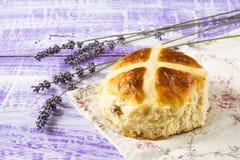 I panini trasversali caldi di Pasqua con lavanda fiorisce sul tovagliolo e sulla tavola bianca e viola di legno Immagini Stock