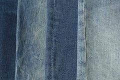 I pantaloni differenti delle ombre delle blue jeans coprono il fondo del mucchio Pila di blue jeans sullo scrittorio del negozio fotografie stock libere da diritti