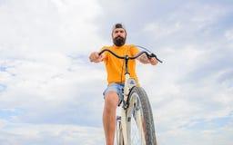 I pantaloni a vita bassa barbuti dell'uomo guidano il fondo del cielo di vista dal basso della bicicletta Consiglio dei meccanici fotografie stock libere da diritti