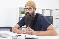 I pantaloni a vita bassa con la barba lunga stanno pensando Fotografie Stock