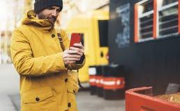 I pantaloni a vita bassa con lo zaino giallo, rivestimento, cappuccio, caffè di termo tenuta della tazza nello smartphone delle m immagine stock libera da diritti