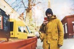 I pantaloni a vita bassa con lo zaino giallo, rivestimento, cappuccio, caffè di termo tenuta della tazza nello smartphone delle m fotografie stock libere da diritti