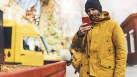 I pantaloni a vita bassa con lo zaino giallo, rivestimento, cappuccio, caffè di termo tenuta della tazza nello smartphone delle m fotografia stock libera da diritti