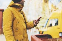 I pantaloni a vita bassa con lo zaino giallo, rivestimento, cappuccio, caffè di termo tenuta della tazza nello smartphone delle m immagini stock libere da diritti