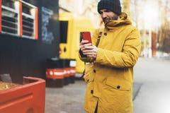 I pantaloni a vita bassa con lo zaino giallo, rivestimento, cappuccio, caffè di termo tenuta della tazza nello smartphone delle m immagine stock