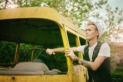 I pantaloni a vita bassa del giovane provano ad ottenere il vecchio retro bus dell'automobile Immagini Stock