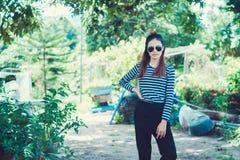 I pantaloni a vita bassa della donna con gli occhiali da sole adattano il concetto di stile di vita di stile, portante una maglie Fotografie Stock Libere da Diritti