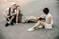 I pantaloni a vita bassa delle donne e del giovane hanno un resto sulla strada Fotografie Stock Libere da Diritti