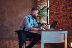 I pantaloni a vita bassa tatuati bei in camicia e bretelle che si siedono allo scrittorio, lavorante ad un computer portatile, te Immagine Stock Libera da Diritti