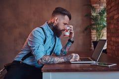I pantaloni a vita bassa tatuati bei in camicia e bretelle che si siedono allo scrittorio, lavorante ad un computer portatile, te Fotografia Stock Libera da Diritti