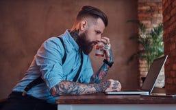 I pantaloni a vita bassa tatuati bei in camicia e bretelle che si siedono allo scrittorio, lavorante ad un computer portatile, te Immagine Stock