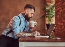 I pantaloni a vita bassa tatuati bei in camicia e bretelle che si siedono allo scrittorio, lavorante ad un computer portatile, te Fotografia Stock