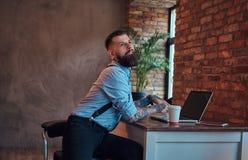 I pantaloni a vita bassa tatuati divertenti in camicia e bretelle che si siedono allo scrittorio, lavorante ad un computer portat Fotografia Stock