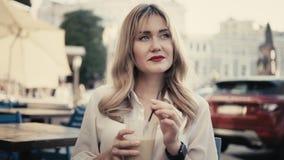 I Paris den unga caucasian blonda kvinnan ilar lockigt hår, med sexiga röda kanter och klockan som dricker en coctail till och me lager videofilmer