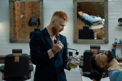 I parrucchieri lavorano per un tipo bello al negozio di barbiere Balsamo sulle parti del corpo asciutte per idratare pelle Cera d immagini stock libere da diritti