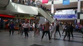 I partecipanti ad un flash di ballo assalgono alla stazione ferroviaria della città centrale stock footage