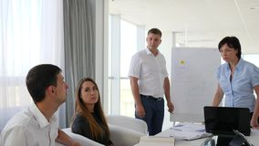 I partner che si siedono alla tavola alla riunione nell'ufficio bianco e spazioso ed ascoltano due genti archivi video