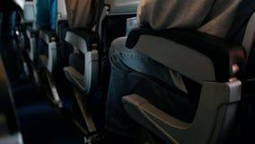 I passeggeri a bordo degli aerei fissano le loro cinture di sicurezza - preparando decollare video d archivio