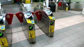 I passeggeri camminano tramite il portone di uscita di zona di produzione di prezzo della stazione della metropolitana video d archivio