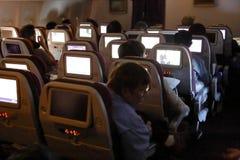 I passeggeri dell'aeroplano guardano la TV sulla direzione da Los Angeles a Seoul Corea del Sud - novembre 2013 Immagine Stock