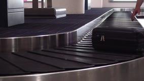I passeggeri irriconoscibili raccolgono il loro bagaglio dal nastro trasportatore Viaggiatori che prendono i loro bagagli nel bag stock footage
