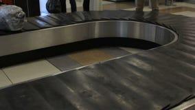 I passeggeri prendono i loro bagagli dalla cinghia nell'aeroporto Area di reclamo di bagaglio stock footage