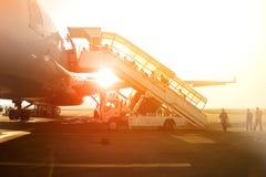 I passeggeri salgono la scala per imbarcarsi su un grande aereo di linea all'aeroporto Immagine Stock