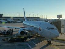 I passeggeri sbarcano fuori da un aeroplano di American Airlines messo in bacino all'UFS di San Francisco International Airport fotografia stock