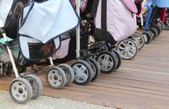 I passeggiatori per i bambini hanno parcheggiato sul pavimento di parquet di legno Fotografia Stock