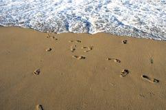 I passi scalzi sulla spiaggia dell'oceano insabbiano ed ondeggiano Fotografia Stock Libera da Diritti