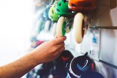 I pattini di rullo dell'assortimento nel negozio del deposito, persona che sceglie e comprare il colore pattina sul chiarore del  fotografie stock libere da diritti