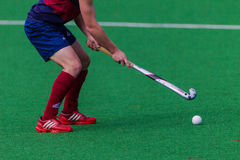 I pattini rossi del giocatore di hokey attaccano la sfera Fotografie Stock