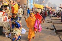 I pellegrini femminili aggiungono il colore lungo la Banca del Gange Fotografia Stock