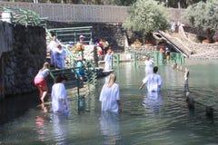 I pellegrini prendono il battesimo nelle acque della Giordania fotografia stock