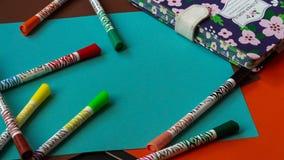 I pennarelli multicolori si trovano su cartone luminoso variopinto accanto al blocco note fotografia stock