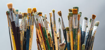 I pennelli su un fondo e su un artista della sfuocatura sta tenendo la spazzola Fotografia Stock