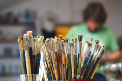 I pennelli su un fondo e su un artista della sfuocatura sta tenendo la spazzola Fotografie Stock Libere da Diritti