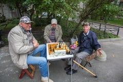 I pensionati giocano gli scacchi nel cortile di una costruzione di appartamento Immagini Stock Libere da Diritti