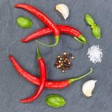 I peperoncini rossi roventi dei peperoncini che cucinano gli ingredienti quadrano le sedere dell'ardesia Fotografie Stock Libere da Diritti