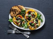 I peperoni dolci al forno hanno farcito l'insalata greca - gli aperitivi deliziosi, spuntini su un fondo scuro immagini stock