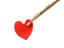 I perni di legno intrappolano il cuore rosso Fotografia Stock