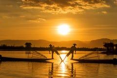 I pescatori di Inle sono conosciuti per la pratica dello stile distintivo di rematura che comprende stare alla poppa su una gamba fotografia stock