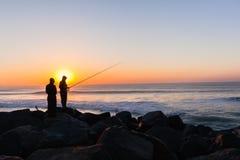 I pescatori hanno profilato l'alba della spiaggia dell'oceano Immagini Stock