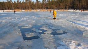 I pescatori hanno tagliato il ghiaccio sul lago per fornire l'ossigeno al pesce, tagliente il ghiaccio su un lago e facente gli s archivi video