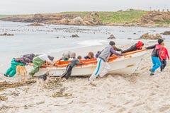 I pescatori muove la loro barca verso sopra il segno di alta marea Fotografia Stock Libera da Diritti